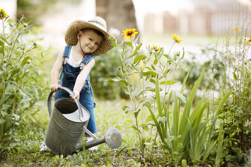 有喷壶的小男孩在夏天公园 免版税库存图片