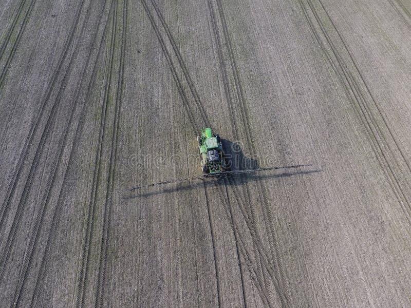 有喷洒的杀虫剂取决于的系统的拖拉机  施肥与拖拉机,以湿剂的形式,在冬天w的领域 库存图片