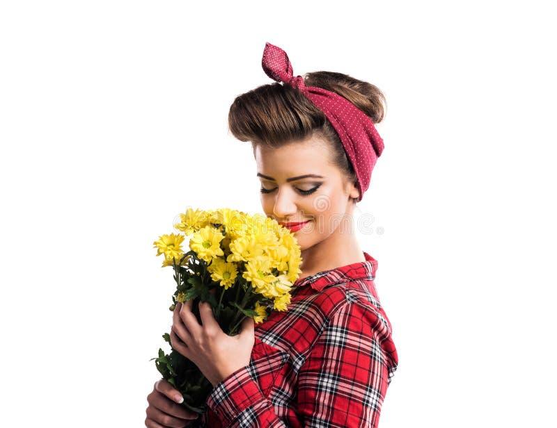 有嗅到黄色雏菊的画报构成和发型的妇女 库存照片