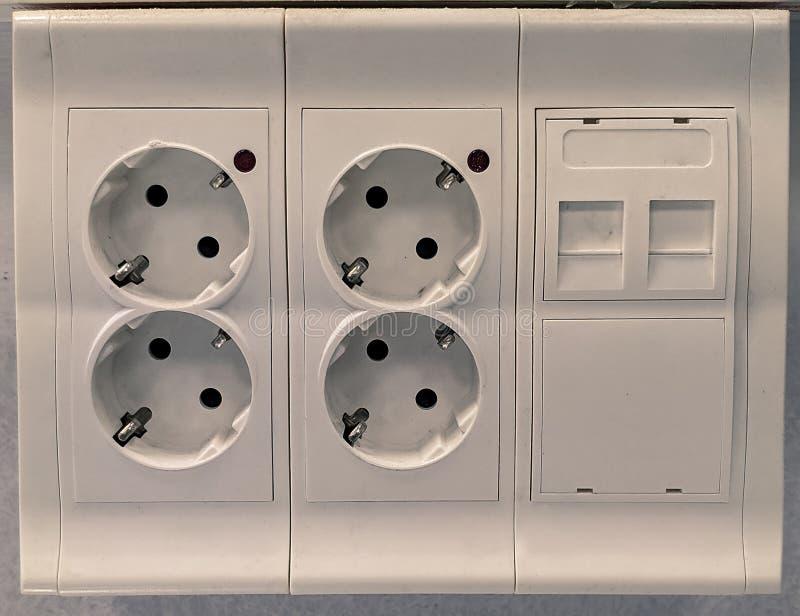 有四个插座和2个声音和数据插口的白色工作站 库存照片