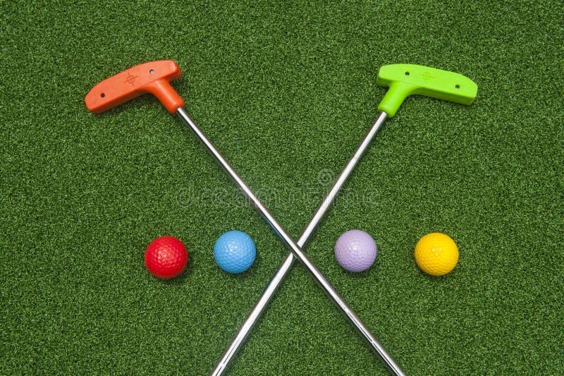 有四个球的横渡的微型高尔夫球轻击棒 图库摄影