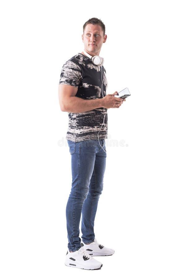 有回顾在肩膀的耳机和手机的年轻时髦的成人人 库存照片