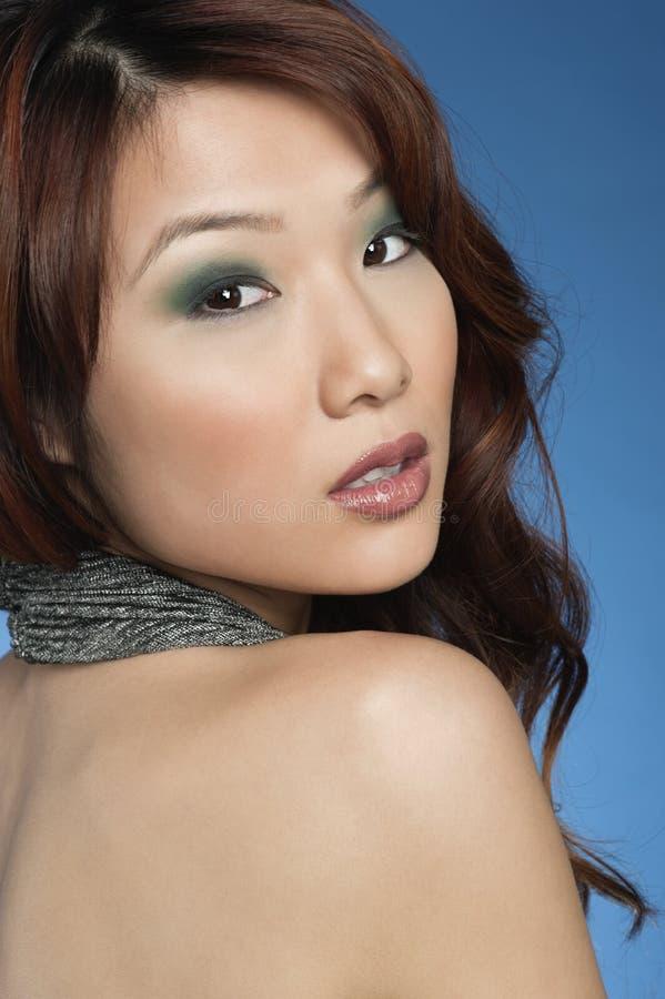 有回顾在色的背景的眼影的美丽的少妇 免版税库存图片