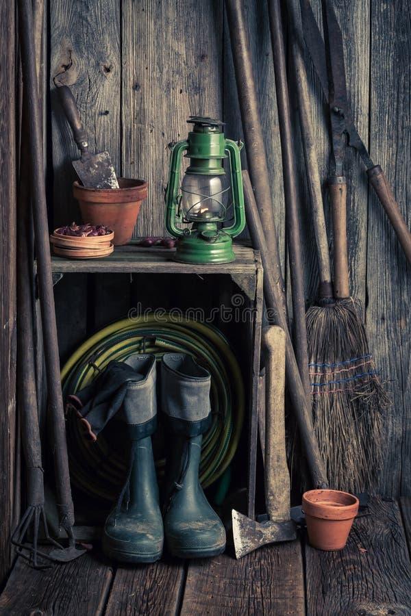 有园艺工具和泥罐的一个老土气棚子 库存照片