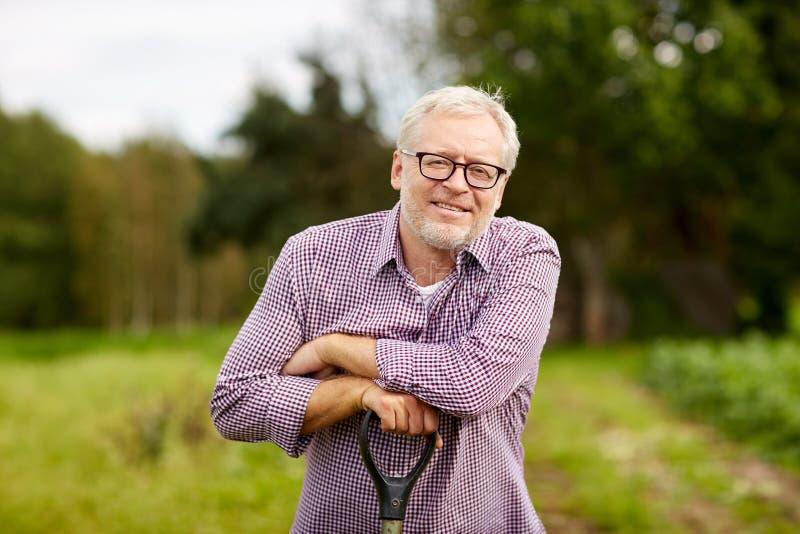 有园艺工具的愉快的微笑的老人在农场 库存图片