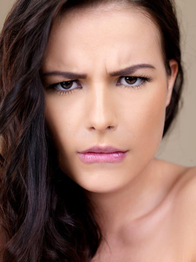 有困惑的皱眉的可爱的妇女 库存照片
