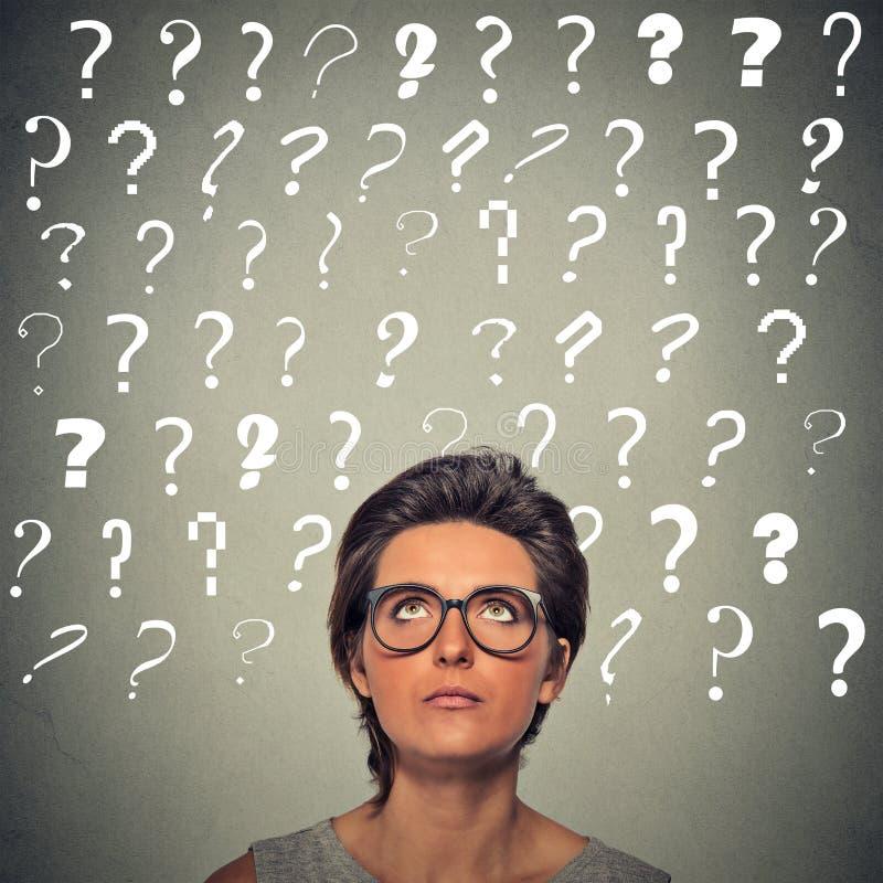 有困惑的面孔表示和问号的妇女在她的头上 免版税库存照片