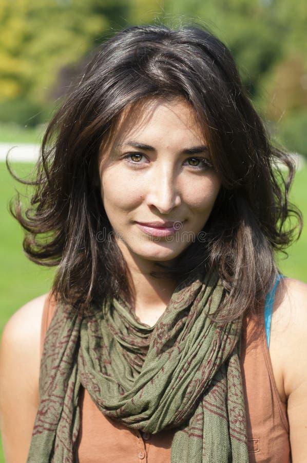 有围巾的美丽的女孩在草坪 图库摄影