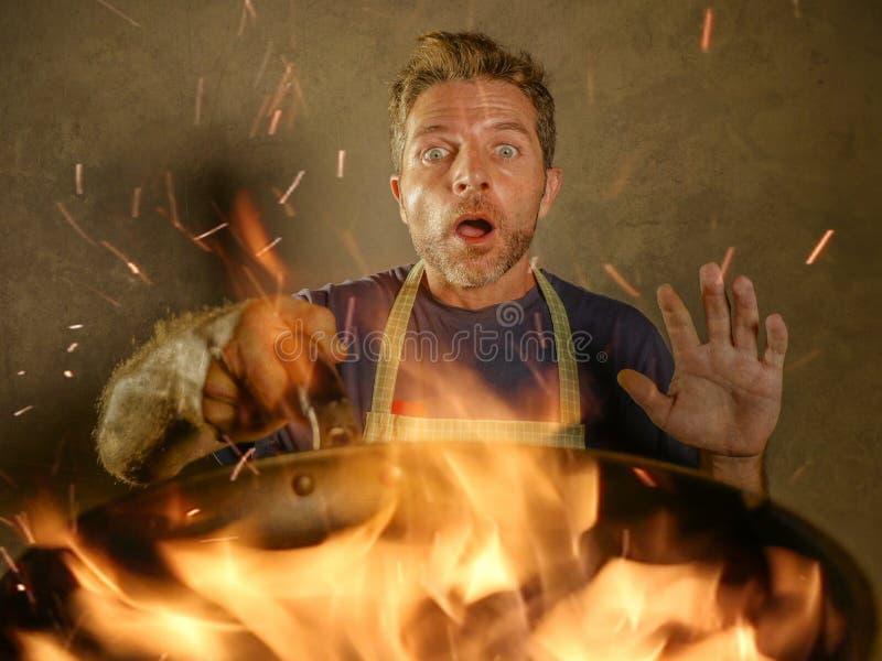 有围裙的年轻滑稽和杂乱家庭厨师人在拿着在火的震动平底锅烧在厨房灾害和国内厨师的食物 库存照片