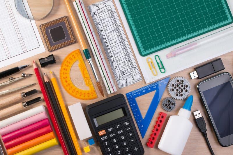 有固定式的学校或办公室工具的书桌 平的位置套艺术家学校文具演播室在学校桌背景射击了 免版税库存图片