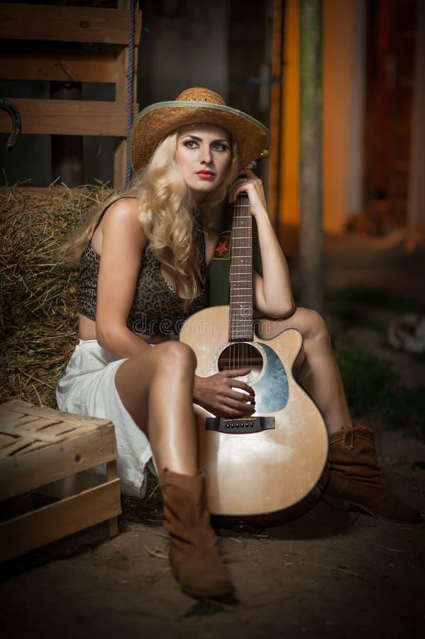 有国家神色的可爱的妇女,户内射击了,美国乡村模式 有秸杆牛仔帽和吉他的白肤金发的女孩 公平的头发 免版税库存图片