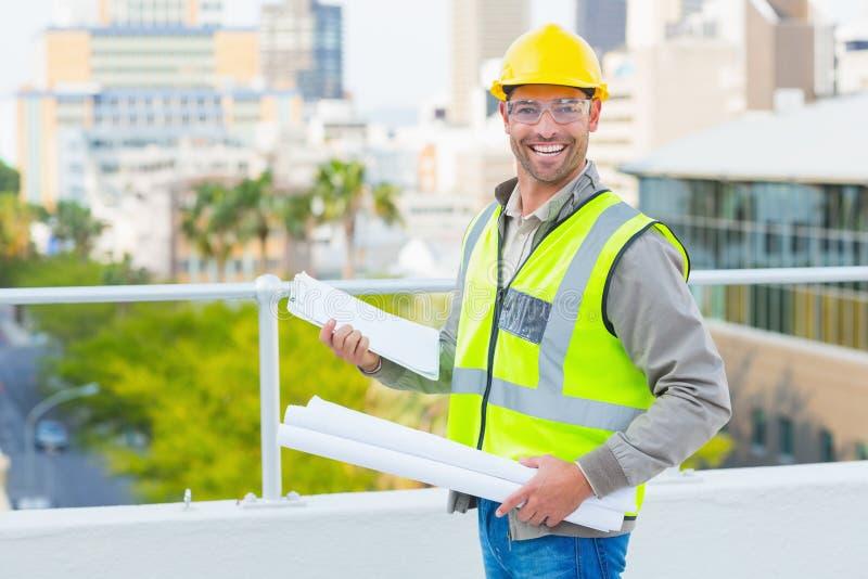 有图纸和剪贴板的微笑的男性建筑师 免版税库存图片