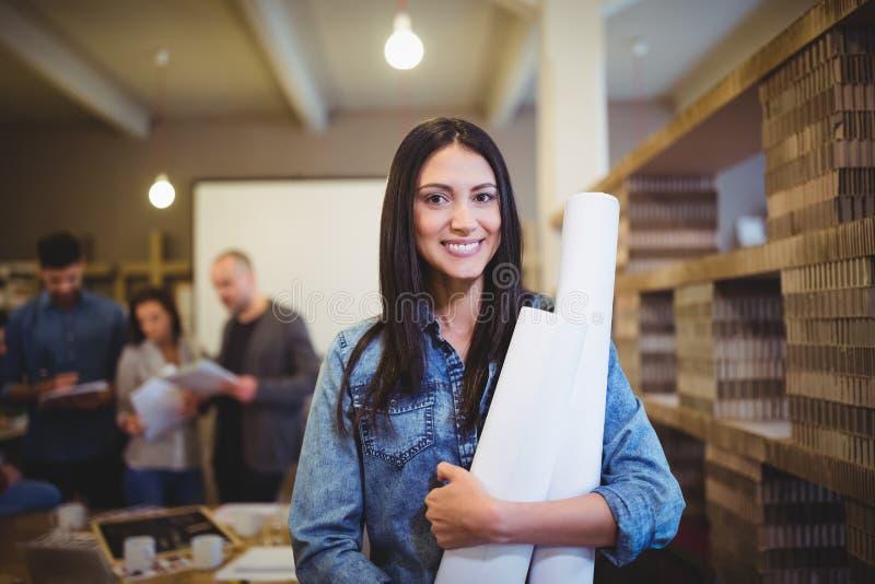 有图纸的女性建筑师,当同事在背景中时 免版税库存照片