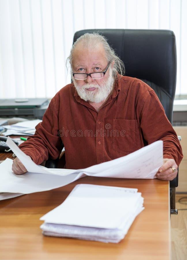 有图纸的建筑师在他的工作,变老了白种人人白领工人 免版税图库摄影