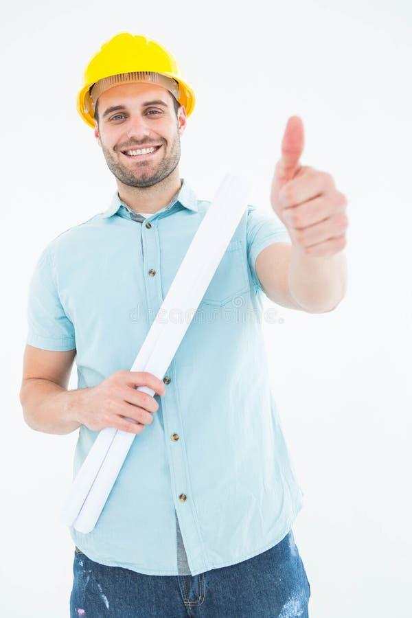 有图纸的男性建筑师打手势赞许的 免版税库存图片