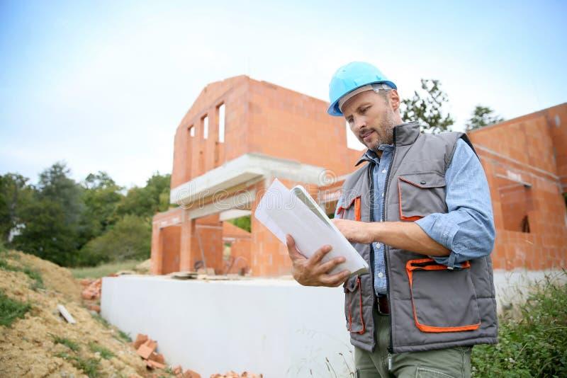 有图纸的建筑经理在建造场所前面 免版税库存照片