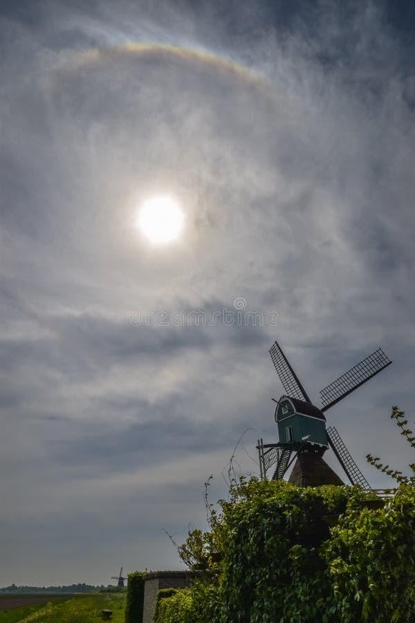 有圆光晕的荷兰风车在太阳附近 库存照片