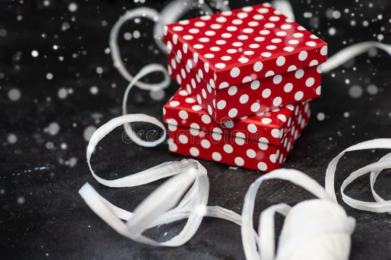 有圆点的礼物盒和黑表面上的白色丝带 免版税库存图片