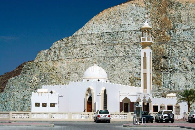 有圆顶的白色清真寺和尖塔在岩石墙壁前面的阿曼 免版税库存图片