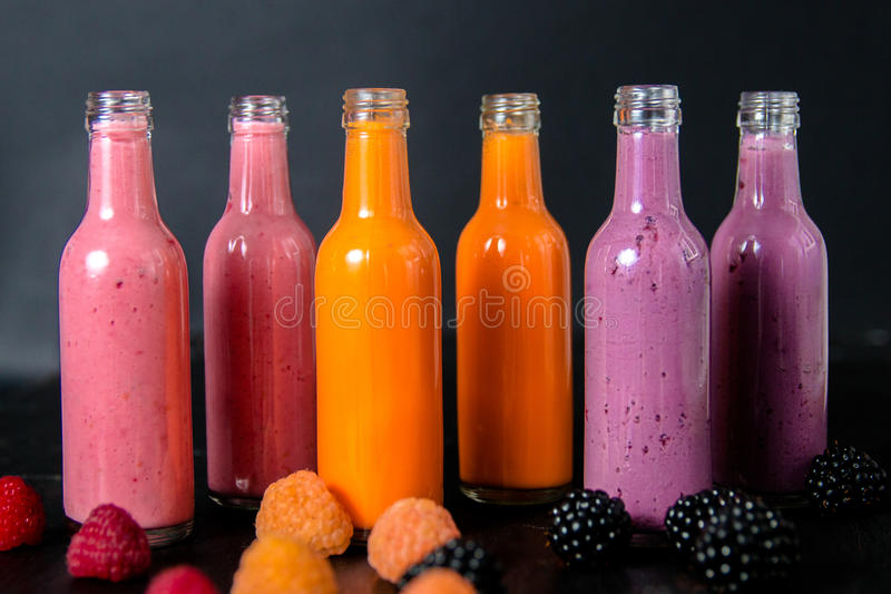 有圆滑的人和莓的,红色,黄色,在黑背景的黑莓六个瓶 在玻璃瓶子莓果的奶昔 饮食或ve 图库摄影