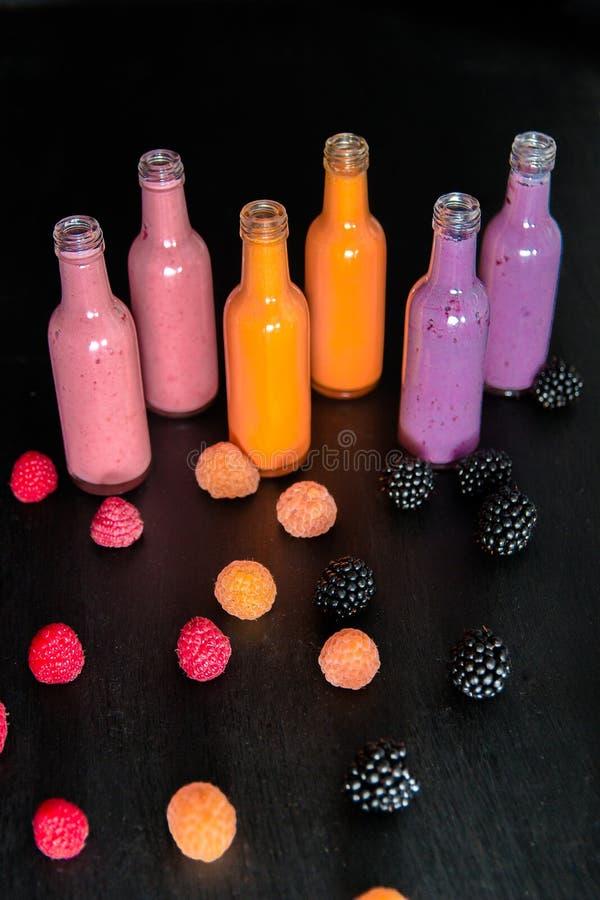 有圆滑的人和莓的,红色,黄色,在黑背景的黑莓六个瓶 在玻璃瓶子莓果的奶昔 饮食或ve 免版税库存图片