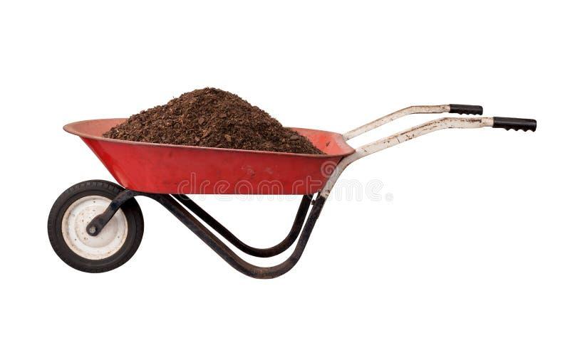 有土壤的生锈的红色独轮车 库存照片
