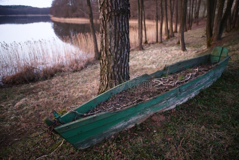 有土壤的老绿色小船在它在棕色秋天湖背景中 库存图片