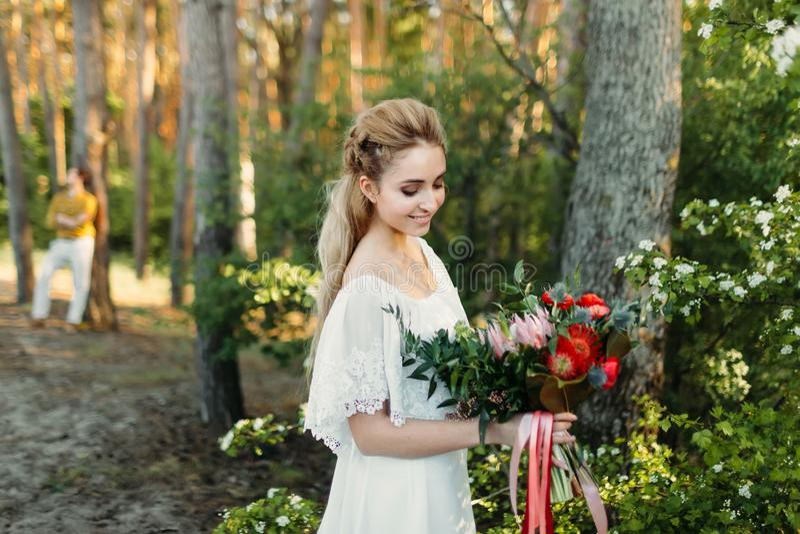有土气花束的年轻白肤金发的新娘是摆在室外在公园 附庸风雅 秋天户外婚礼 免版税库存照片