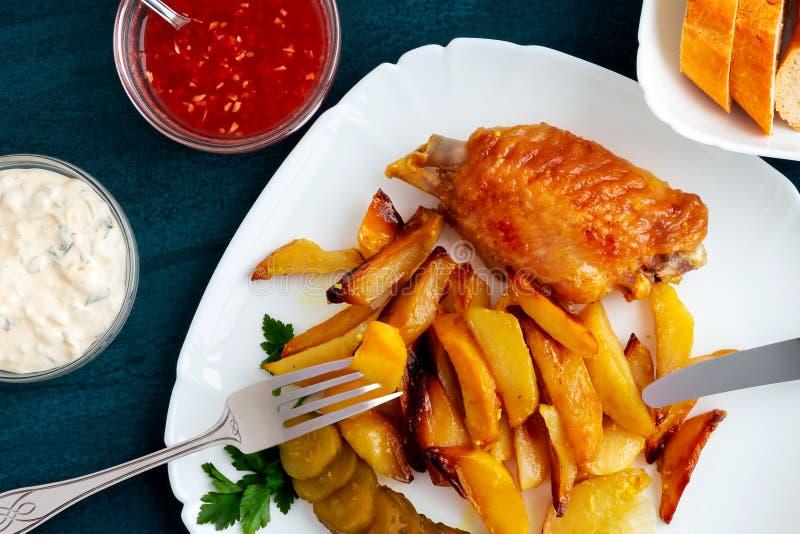 有土豆片的被烘烤的火鸡翅在黑厨房用桌上的一块白色板材用调味汁和西红柿酱和 免版税库存照片
