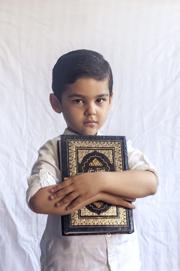 有圣洁古兰经的一个年轻中东男孩 5岁画象拿着一个圣洁古兰经有白色背景的回教孩子 免版税库存图片