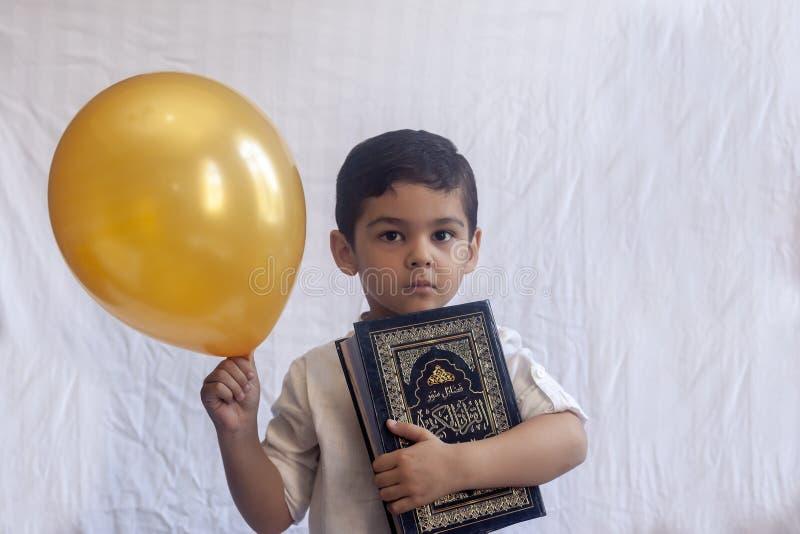 有圣洁古兰经的一个年轻中东男孩 5岁画象拿着一个圣洁古兰经有白色背景的回教孩子 库存照片