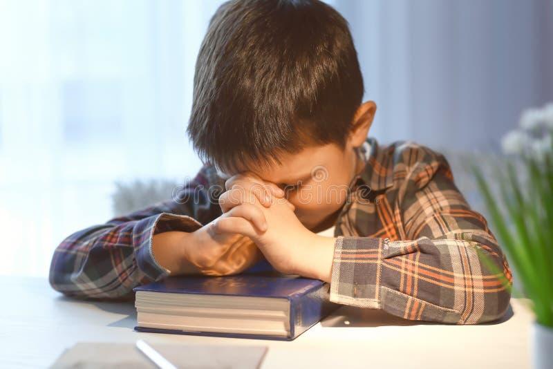 有圣经的在家祈祷的小男孩 库存照片
