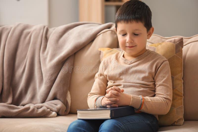 有圣经的在家祈祷的小男孩 免版税库存图片