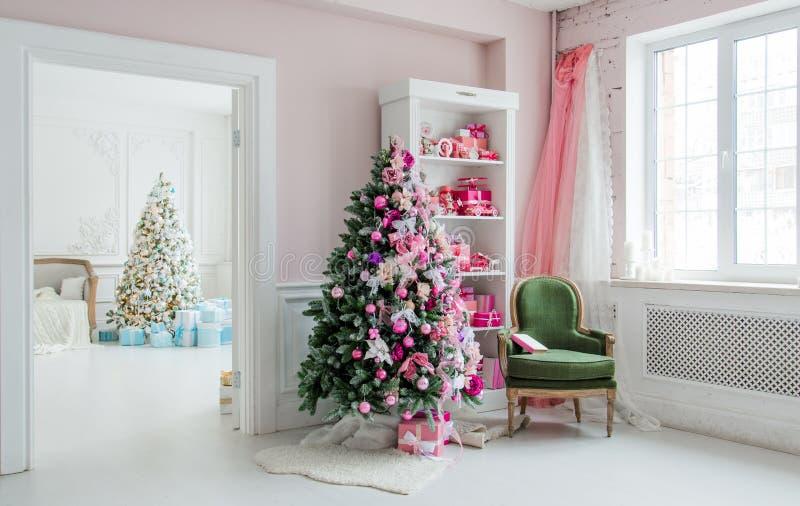 有圣诞树、架子和桃红色蓝色礼物的对此,绿色椅子家内部美好的holdiay装饰的房间 免版税图库摄影