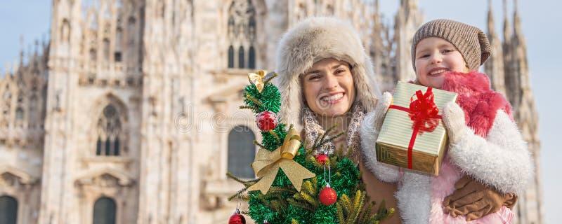 有圣诞树和礼物的母亲和儿童游人在米兰 免版税库存图片