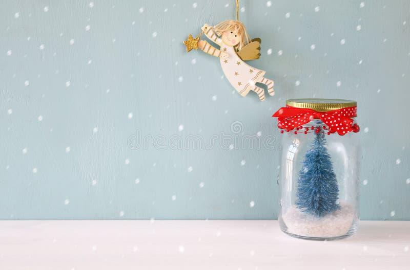有圣诞树和飞行天使的金属螺盖玻璃瓶 免版税库存图片