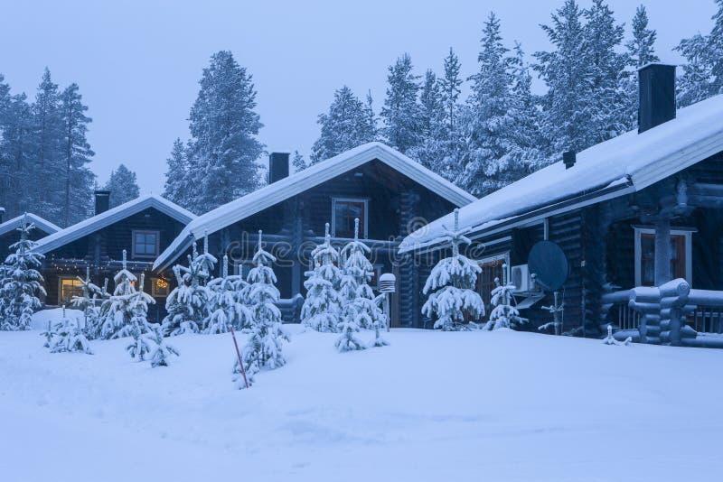 有圣诞树的三舒适木议院在位于平静的美丽如画的北欧森林的前面 免版税库存图片