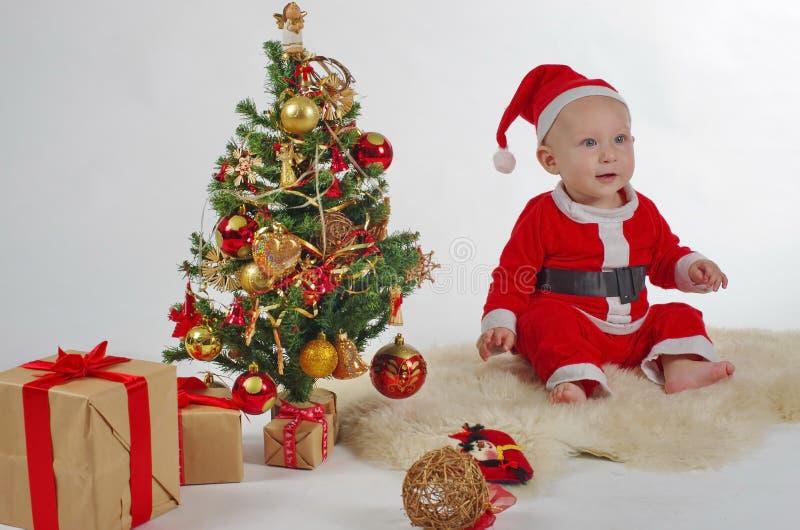 有圣诞树的圣诞老人婴孩 库存照片