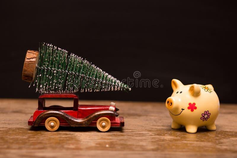 有圣诞树的存钱罐和玩具汽车在黑暗的土气背景的木头与拷贝空间 免版税库存图片