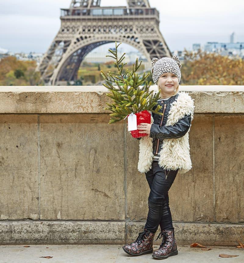 有圣诞树的愉快的现代女孩在巴黎,法国 免版税图库摄影