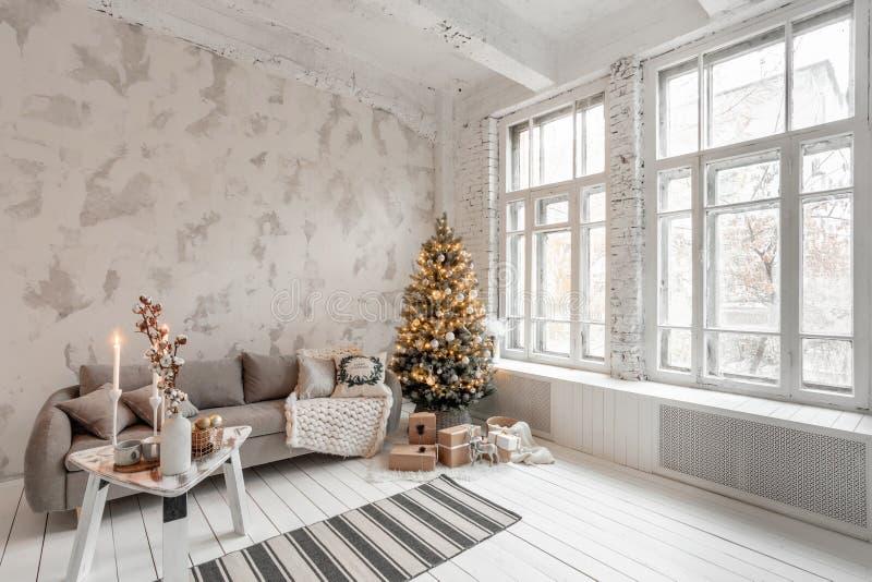 有圣诞树的轻的客厅 舒适的沙发,高大Windows  免版税库存图片