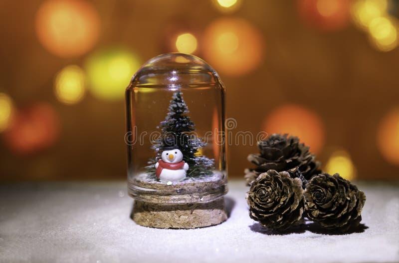 有圣诞树的雪人在杉木锥体附近的玻璃管从圣诞灯背景 免版税图库摄影
