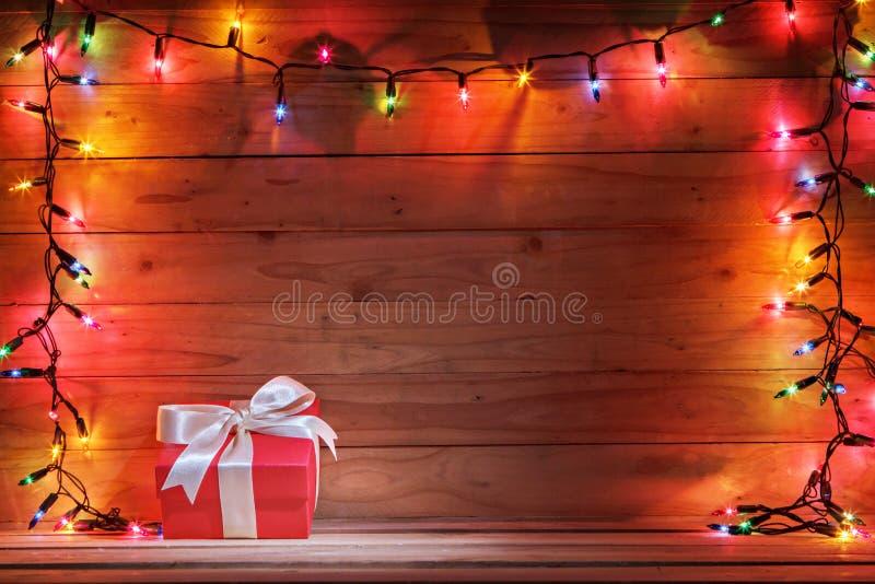 有圣诞灯和木背景的礼物盒 图库摄影