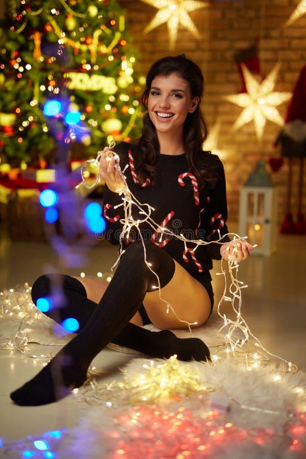 有圣诞灯的美丽的愉快的少妇 库存照片