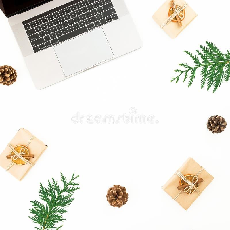 有圣诞礼物、常青分支和杉木锥体的膝上型计算机在白色背景 假日办公室构成 顶视图 平的位置 库存图片