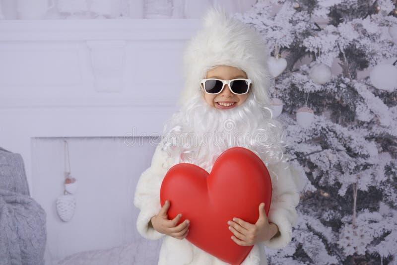 有圣诞礼物和圣诞树的一个孩子 图库摄影