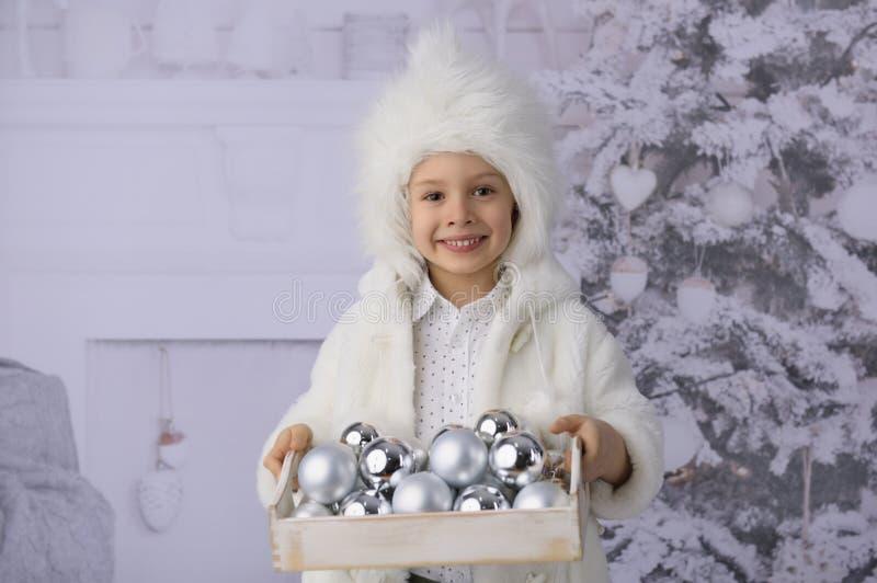 有圣诞礼物和圣诞树的一个孩子 库存图片