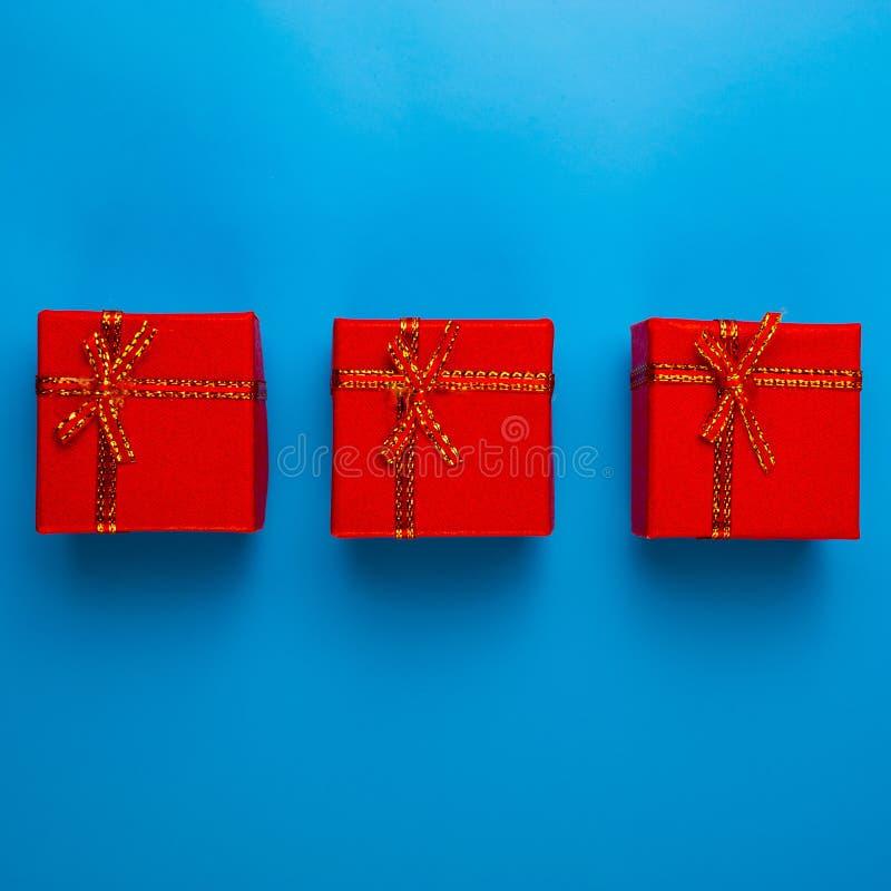有圣诞礼物的三个红色箱子在蓝色背景说谎 免版税库存图片