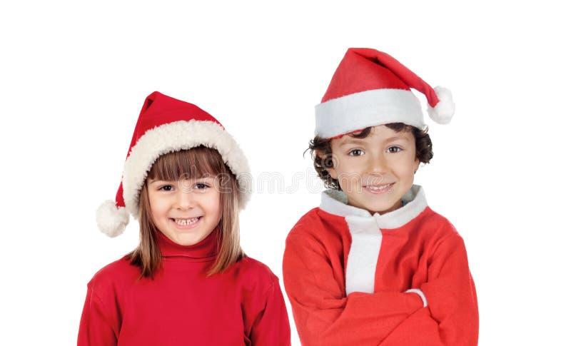 有圣诞老人帽子和红色衣裳的愉快的孩子 免版税库存照片