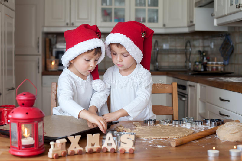 有圣诞老人帽子的两个逗人喜爱的男孩,准备曲奇饼在厨房里 库存图片